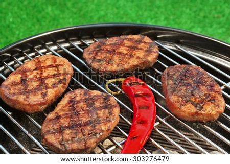 Close-up Of BBQ Hamburger Patties And Chili Pepper On The Hot Charcoal Grill. Vibrant Backyard Lawn In The Background. Cookout Food For Summer Weekend Picnic Or Party. - stock photo