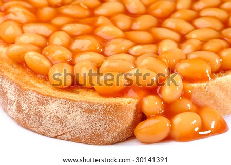 Close up of beans on toast with some beans dripping off the side of toast - stock photo