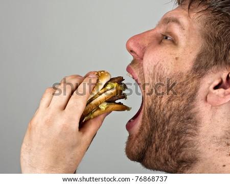 Close-up of bearded man eating juicy hamburger - stock photo