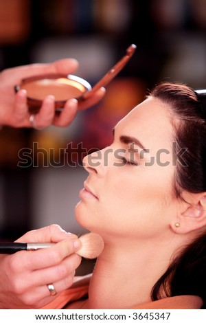 Close up of beautician creating makeup for a young women in the beauty parlour. - stock photo