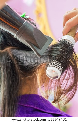 Close up of beautician's hand setting the hair properly after haircut - stock photo
