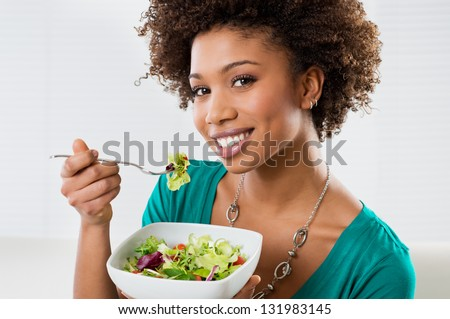 Close-up Of Beautiful African American Woman Eating Salad At Home - stock photo