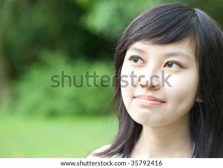 Close up of Beautiful Asian Chinese/Japanese girl daydreaming for ideas outdoors - stock photo