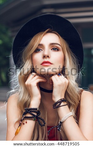 Close up of beautiful blonde woman with black hat, looking at camera and touching her long curly golden hair. She is wearing red t-shirt, around neck she has black choker and on hands many bracelets.