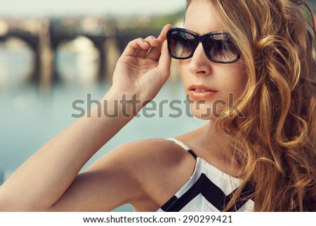 Close up of beautiful blonde young woman wearing fashionable clothes and black sunglasses posing in the city. Fashion photo - stock photo
