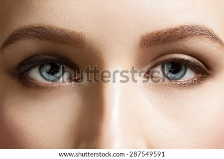 Close-up of beautiful blue eyes woman with brown eyebrows and black lashes - stock photo