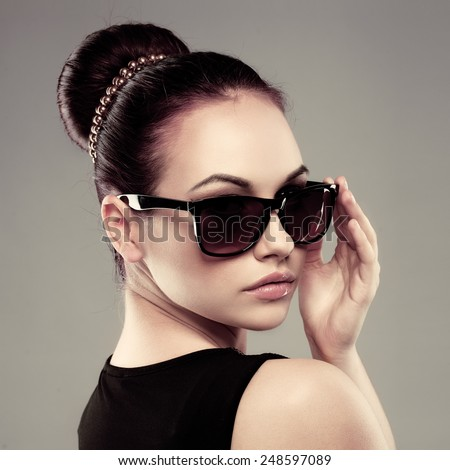 Close-up of beautiful brunette model in stylish black sunglasses. Young pretty female with retro hairdo posing in studio.  - stock photo