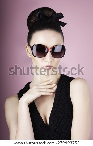 Close-up of beautiful brunette model in stylish black sunglasses. Young pretty female with retro hairdo posing in studio.