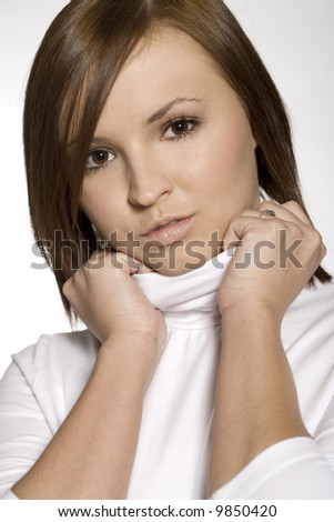 close-up of beautiful brunette young girl wearing white blouse on light background