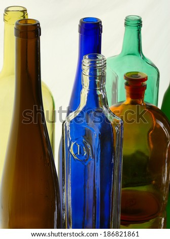 close-up of beautiful colorful empty bottles without caps isolated on white background studio - stock photo