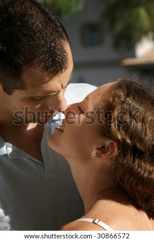close up of beautiful couple smiling about to kiss outside - stock photo