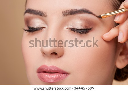 Close up of beautiful face of young woman getting make-up. The artist is applying eyeshadow on her eyebrow with brush. The lady closed eyes with relaxation - stock photo