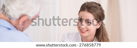 Close-up of beautiful female carer taking care about her older ward - stock photo