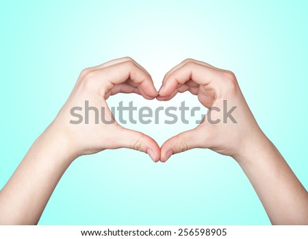 Close up of beautiful female hands form heart shape isolated on turquoise background - stock photo
