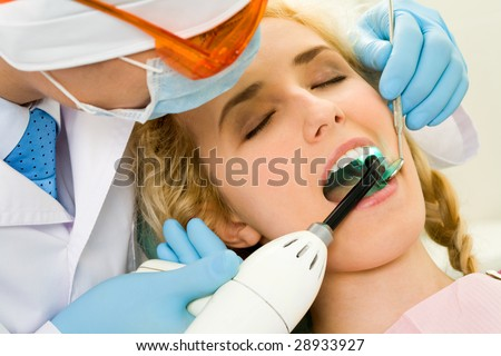 Close-up of beautiful female with open mouth having her teeth healed - stock photo