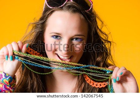 Close-up of beautiful girl and necklace, make-up, yellow background