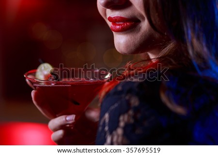 Close-up of beautiful girl having a drink in bar - stock photo