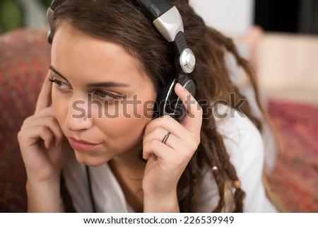 Close-up of beautiful girl in headphones enjoying the music - stock photo
