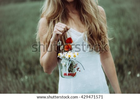 Close up of beautiful girl with flower in the summer park. Woman picking flowers. - stock photo