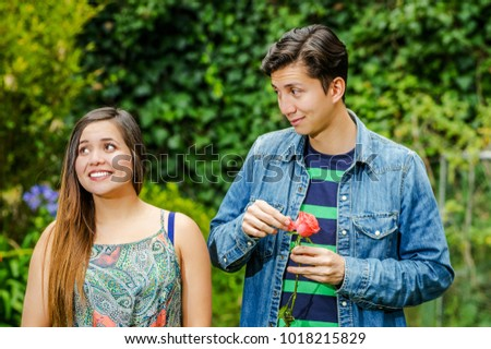 Close up of beautiful inlove young couple in a park, woman smiling while man is playing with a flower and looking at her crush