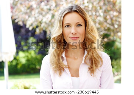 Close-up of beautiful mature woman sitting at garden and smiling.  - stock photo