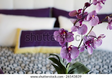 Close up of beautiful orchids with luxurious bedroom bedding in background with copy space. - stock photo