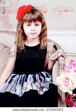 Close-up of Beautiful small girl in black dress  sitting on sofa  - stock photo