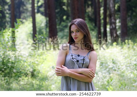 Close-up of beautiful smiling girl in dress and long hair with blurred view of forest in background - stock photo