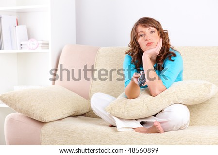 Close-up of beautiful unhappy woman sitting on sofa with remote controller and swiching TV channels. - stock photo