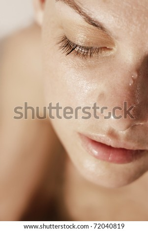 Close-up of beautiful wet woman face with water drop. - stock photo