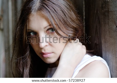 close-up of beautiful woman against a old wooden wall - stock photo