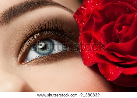 Close-up of beautiful woman eye with red rose and stylish makeup - stock photo