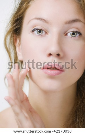 Close-up of beautiful woman face, applying moisturizer - stock photo