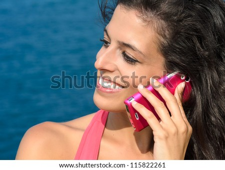 Close up of beautiful woman face talking by cell phone and smiling on blue sea background in summer. Caucasian model using mobile. - stock photo
