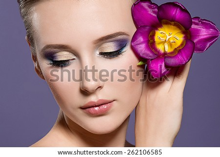 Close-up of beautiful woman face with colorful make-up and lips with bight flower. Woman with tulip. - stock photo