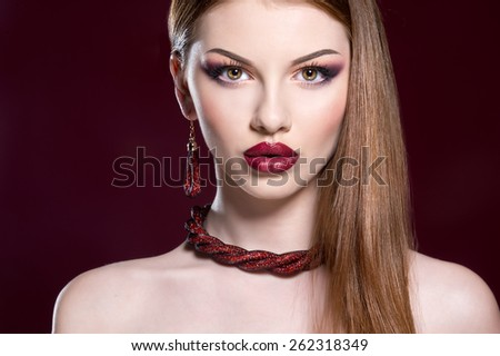 Close-up of beautiful woman face with colorful make-up and red lips - stock photo
