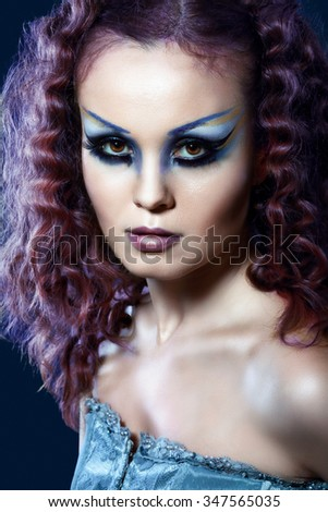 Close-up of beautiful woman face with Creative Fashion Art make up and eyelashes. Studio