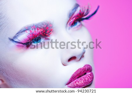 Close-up of beautiful woman face with Creative Fashion Art make up and eyelashes.  Studio - stock photo