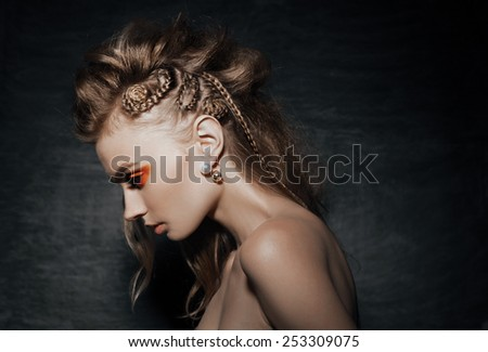 close-up of beautiful woman in fashion pose, braid hairstyle, stylish fashion earings  and creative orange smoky eyes - stock photo
