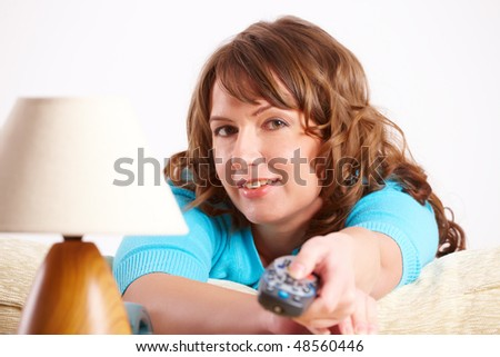 Close-up of beautiful woman laying on sofa with remote controller and switching TV channels. - stock photo