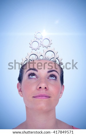 Close-up of beautiful woman looking up against blue background - stock photo