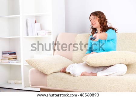 Close-up of beautiful woman sitting on sofa with remote controller and swiching TV channels. - stock photo