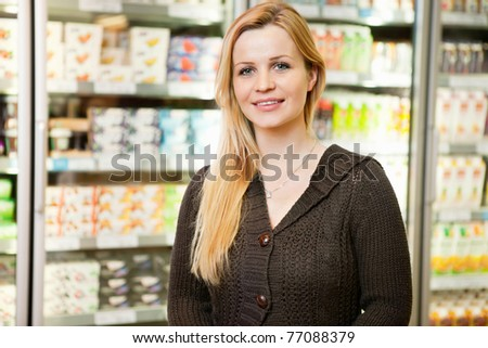 Close-up of beautiful woman smiling and looking at camera in shopping centre - stock photo