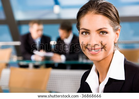 Close-up of beautiful woman smiling on the background of two businesspeople - stock photo