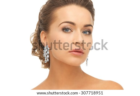 close-up of beautiful woman wearing shiny diamond earrings - stock photo