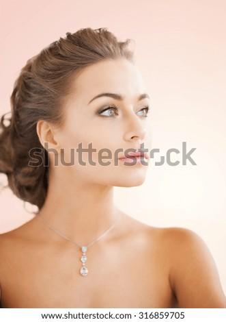 close up of beautiful woman wearing shiny diamond necklace - stock photo