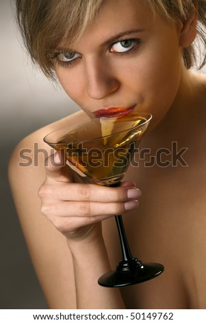 Close-up of beautiful woman with exciting red lips drinking martini cocktail - stock photo