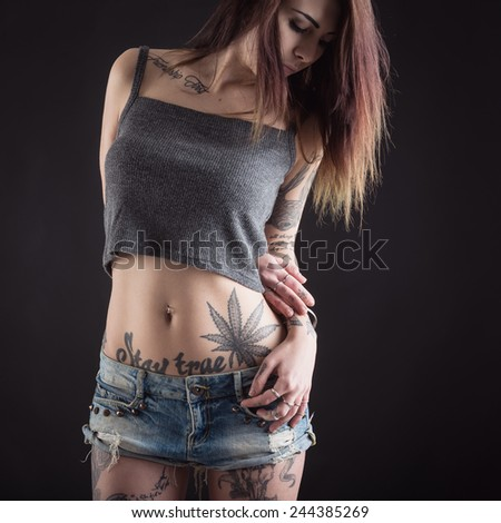 Close up of beautiful woman with tattoo wearing jeans short paint against black background. - stock photo