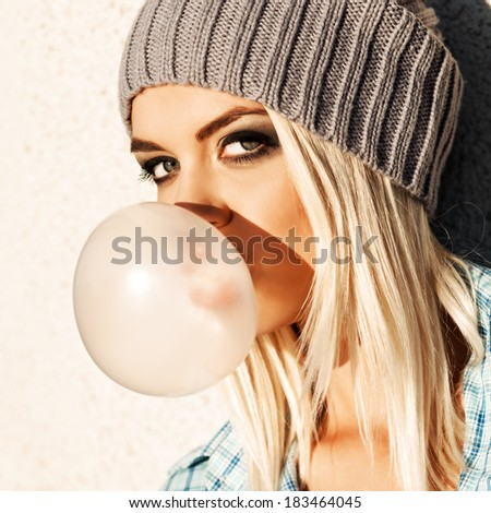 Close-up of beautiful young blond girl in beanie hat blows big bubble from bubble gum - stock photo
