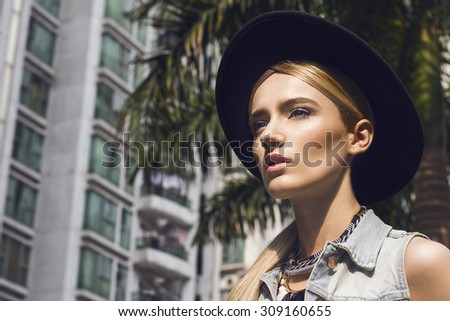 Close up of beautiful young  blonde woman with black hat. Wearing denim vest, necklace and white undershirt. Her hair is tied to ponytail. Professional make-up, hair style and styling. - stock photo